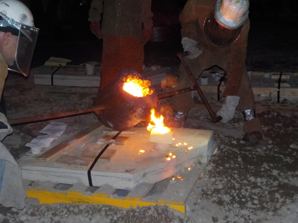 Pouring the molten iron into an artist's mold